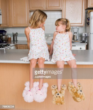 Girls wearing slippers and sleepwear in kitchen : Stock Photo
