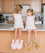 Girls wearing slippers and sleepwear in kitchen