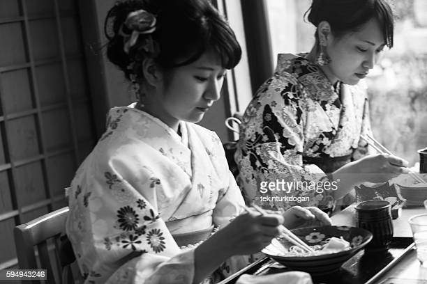 girls wearing traditional kimono eating noodle in kyoto japan
