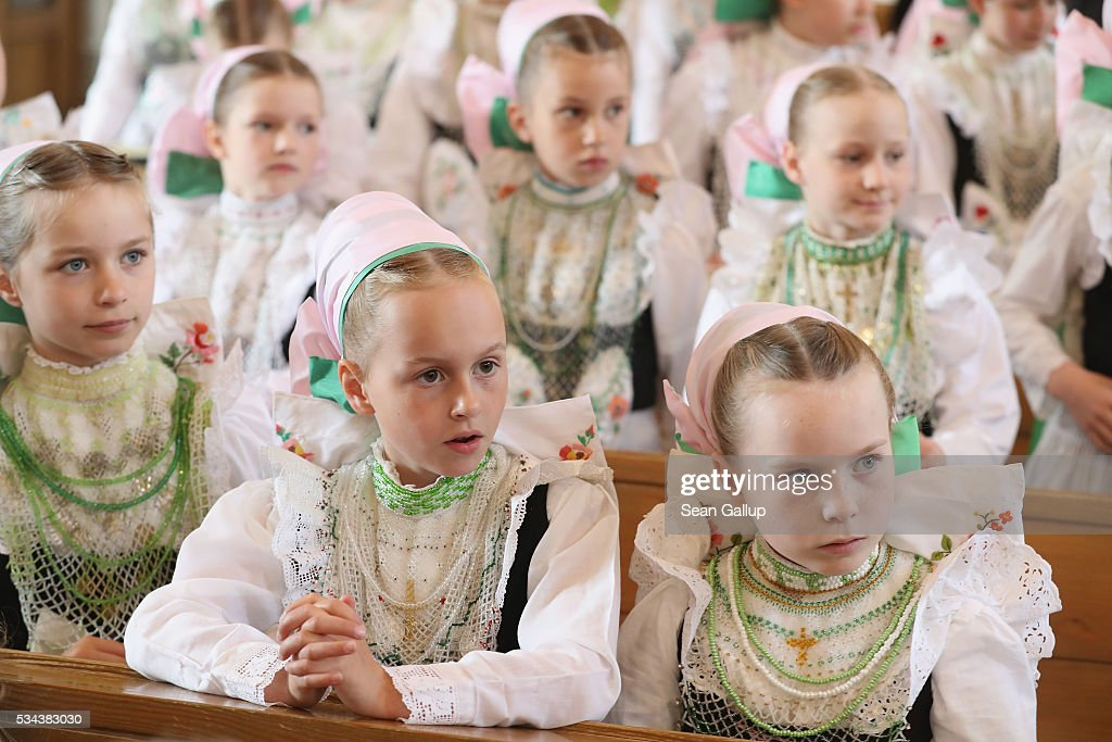 Girls wearing traditional Sorbian festive dress arrive back in church to continue mass following the annual Sorbian Corpus Christi procession on May 26, 2016 in Crostwitz, Germany. Sorbians are a Slavic minority in southeastern Germany who speak a language similar to Czech and Polish. Sorbian is still taughet in some schools in the region and a lively tradition of Sorbian literature, theater and folk culture has survived.