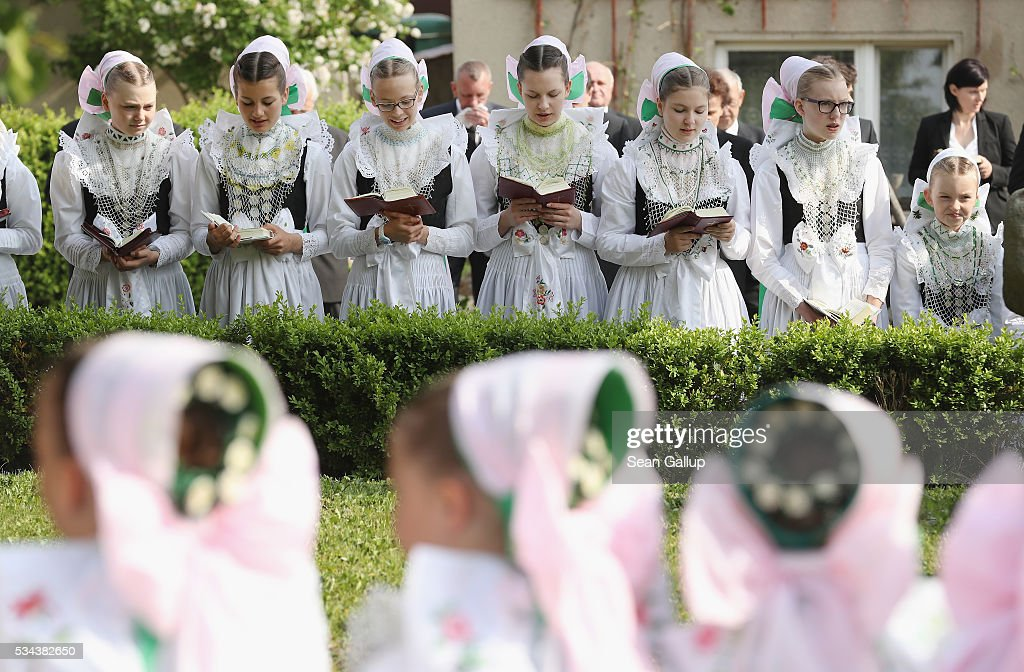 Girls wearing traditional Sorbian festive dress sing from hymn books during an outdoor mass at the annual Sorbian Corpus Christi procession through the village center on May 26, 2016 in Crostwitz, Germany. Sorbians are a Slavic minority in southeastern Germany who speak a language similar to Czech and Polish. Sorbian is still taughet in some schools in the region and a lively tradition of Sorbian literature, theater and folk culture has survived.
