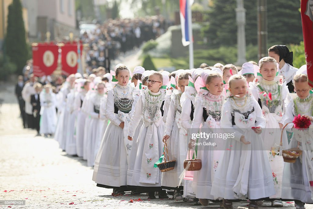 Girls wearing traditional Sorbian festive dress toss flower petals onto the road as they participate in the annual Sorbian Corpus Christi procession through the village center on May 26, 2016 in Crostwitz, Germany. Sorbians are a Slavic minority in southeastern Germany who speak a language similar to Czech and Polish. Sorbian is still taughet in some schools in the region and a lively tradition of Sorbian literature, theater and folk culture has survived.