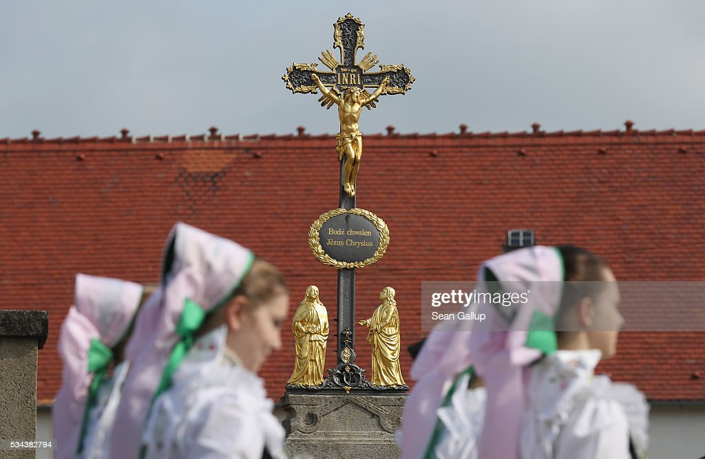 Girls wearing traditional Sorbian festive dress walk past a cross inscribed with text in Sorbian as they participate in the annual Sorbian Corpus Christi procession through the village center on May 26, 2016 in Crostwitz, Germany. Sorbians are a Slavic minority in southeastern Germany who speak a language similar to Czech and Polish. Sorbian is still taughet in some schools in the region and a lively tradition of Sorbian literature, theater and folk culture has survived.