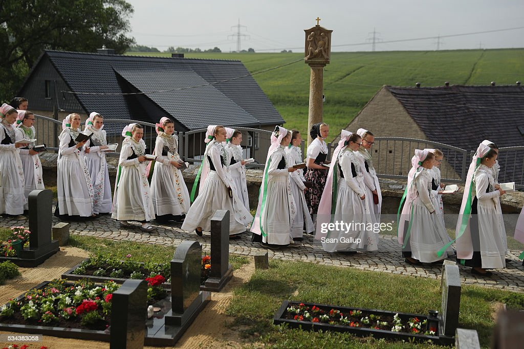 Girls wearing traditional Sorbian festive dress walk through the cemetery of the village church during the annual Sorbian Corpus Christi procession on May 26, 2016 in Crostwitz, Germany. Sorbians are a Slavic minority in southeastern Germany who speak a language similar to Czech and Polish. Sorbian is still taughet in some schools in the region and a lively tradition of Sorbian literature, theater and folk culture has survived.
