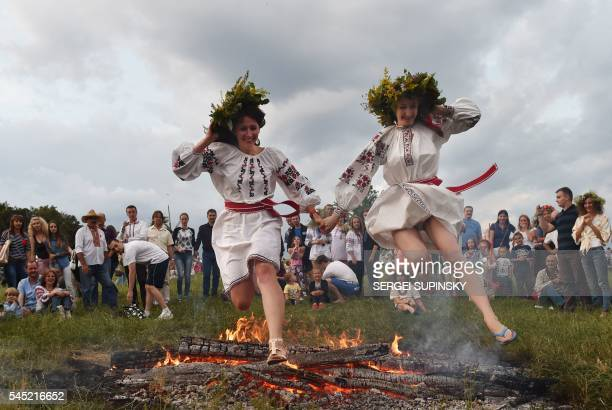 TOPSHOT Girls wearing traditional Ukrainian clothes jump over a bonfire during the Ivana Kupala night an ancient heathen holiday in the Pyrogove...