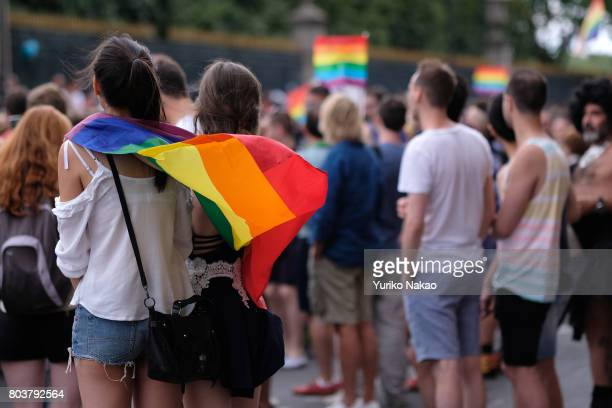 Girls with a rainbow flag commonly known as the gay pride flag or LGBT pride flag watches participants of the Paris Gay Pride Parade or known as...
