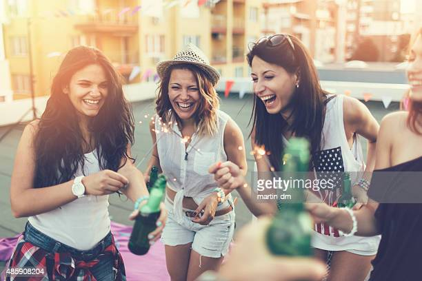 Girls with beer bottles and sparklers on a rooftop party