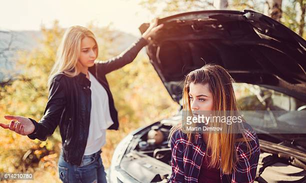 Girls with broken car outside