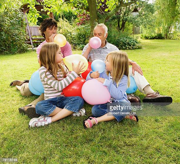 Girls (5-8) with father and grandfather, blowing up balloons in garden
