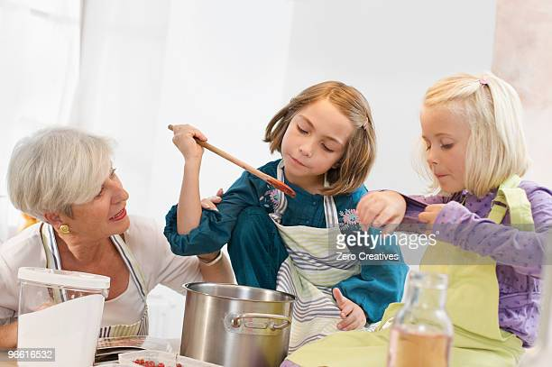 girls with grandmother cooking jam