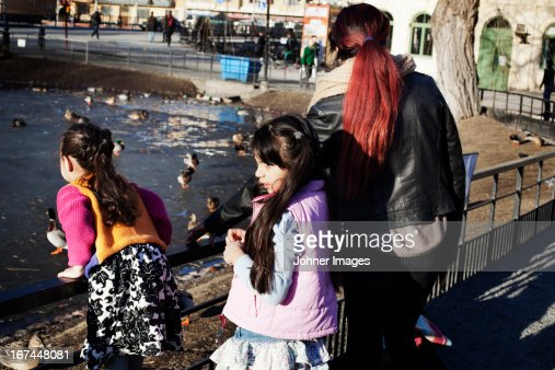 Girls with mother feeding ducks in park : Stock Photo
