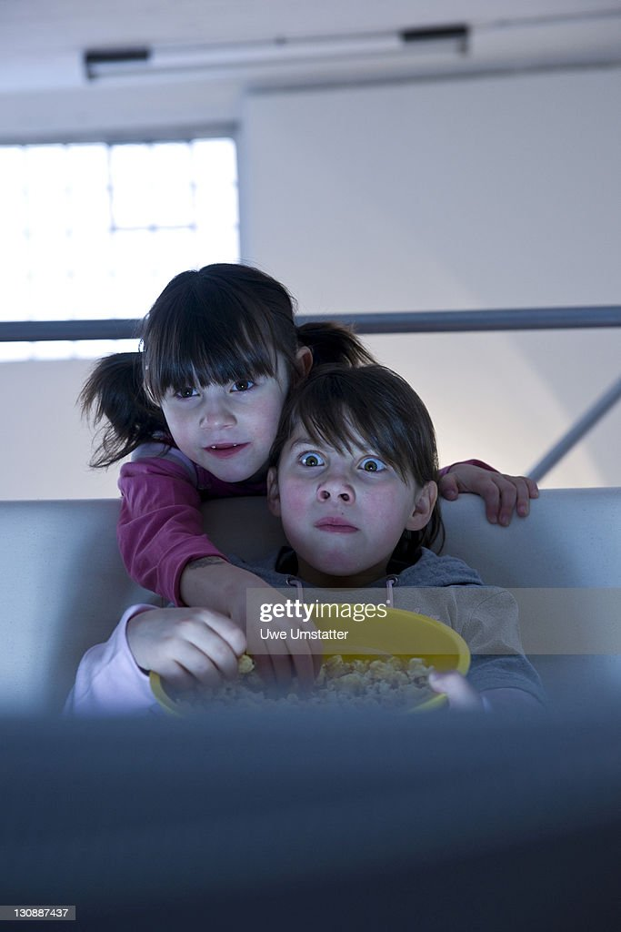 Girls with popcorn watching television : Stock Photo