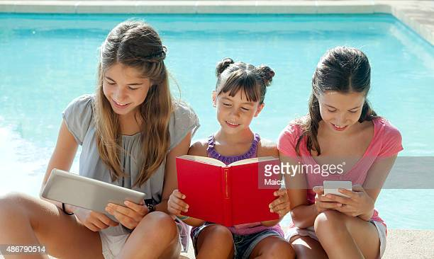 Girls with tablet with phone and book