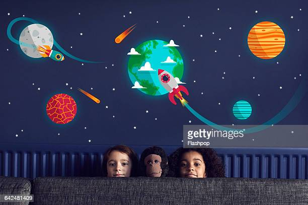 Girls with toy sitting under stars and planets