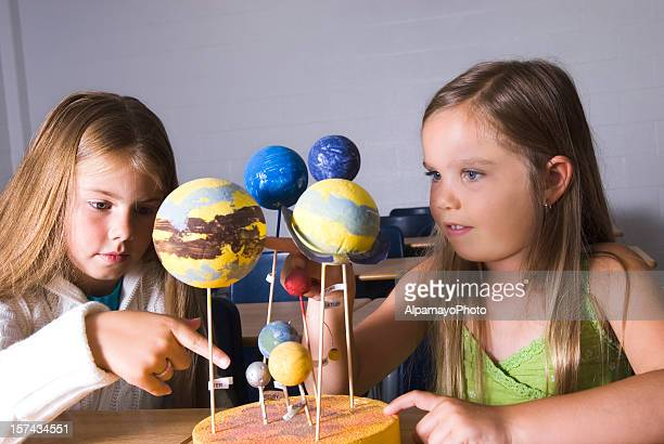 Girls working with space models in the classroom