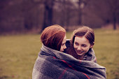 Girls wrapped in a blanket outdoors, smiling