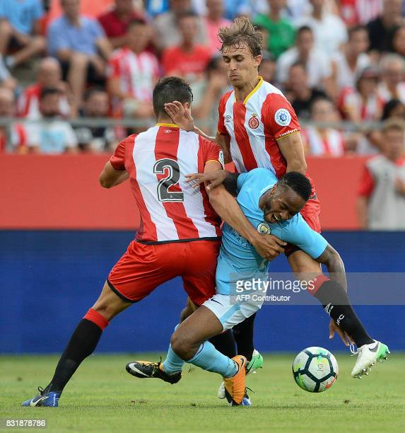 Girona's Colombian defender Bernardo Espinosa and defender Marc Muniesa vie with Manchester City's English midfielder Raheem Sterling during the...
