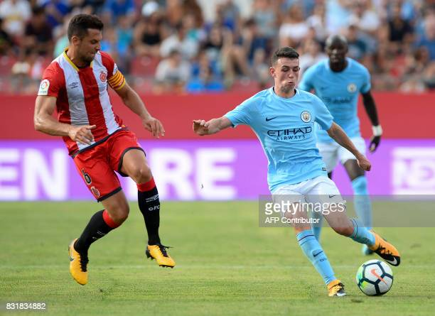 Girona's midfielder Alex Granell vies with Manchester City's midfielder Phil Foden during the Costa Brava trophy friendly football match between...