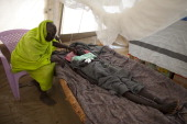 Gisma Hakim suffering from malaria gets touched by her mother trying to cope with her high fever at the MSF field hospital July 17 2012 in Jamam...
