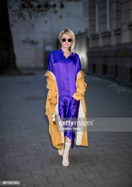 Gitta Banko wearing a dark purple silk shirtdress evening cocktail dress with side pockets by Haider Ackermann wild silk saffroncolored trench coat...