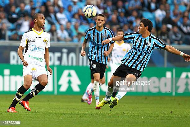 Giuliano of Gremio battles for the ball against Gualberto of Criciuma during the match Gremio v Criciuma as part of Brasileirao Series A 2014 at...