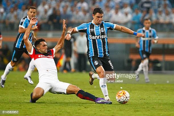 Giuliano of Gremio battles for the ball against Matias Caruzzo of San Lorenzo during the match Gremio v San Lorenzo as part of Copa Bridgestone...