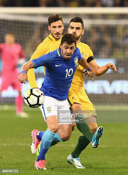 Giuliano Paula of Brazil and Aziz Behich of Australia compete for the ball during the Brasil Global Tour match between Australian Socceroos and...