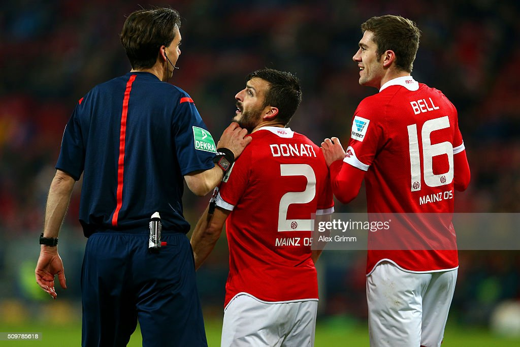 Giulio Donati and Stefan Bell of 1. FSV Mainz 05 speak with referee Manuel Grafe during the Bundesliga match between 1. FSV Mainz 05 and FC Schalke 04 at Coface Arena on February 12, 2016 in Mainz, Germany.