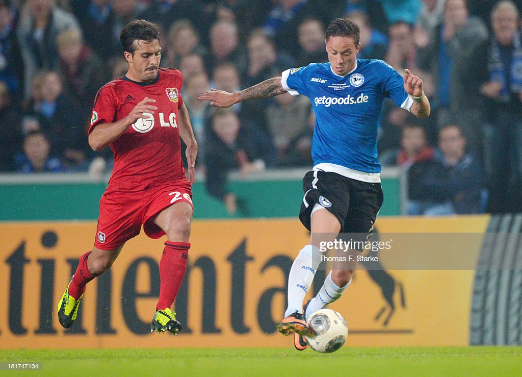Giulio Donati (L) of Leverkusen and <a gi-track='captionPersonalityLinkClicked' href=/galleries/search?phrase=Christian+Mueller&family=editorial&specificpeople=645410 ng-click='$event.stopPropagation()'>Christian Mueller</a> of Bielefeld fight for the ball during the DFB Cup match between Arminia Bielefeld and Bayer 04 Leverkusen at Schueco Arena on September 24, 2013 in Bielefeld, Germany.