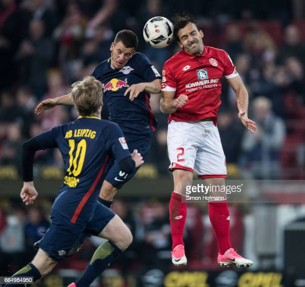 Giulio Donati of Mainz jumps for a header with Diego Demme of Leipzig during the Bundesliga match between 1 FSV Mainz 05 and RB Leipzig at Opel Arena...