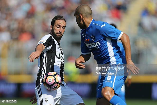 Giuseppe Bellusci of Empoli FC battles for the ball with Gonzalo Higuian of Juventus FC during the Serie A match between Empoli FC and Juventus FC at...