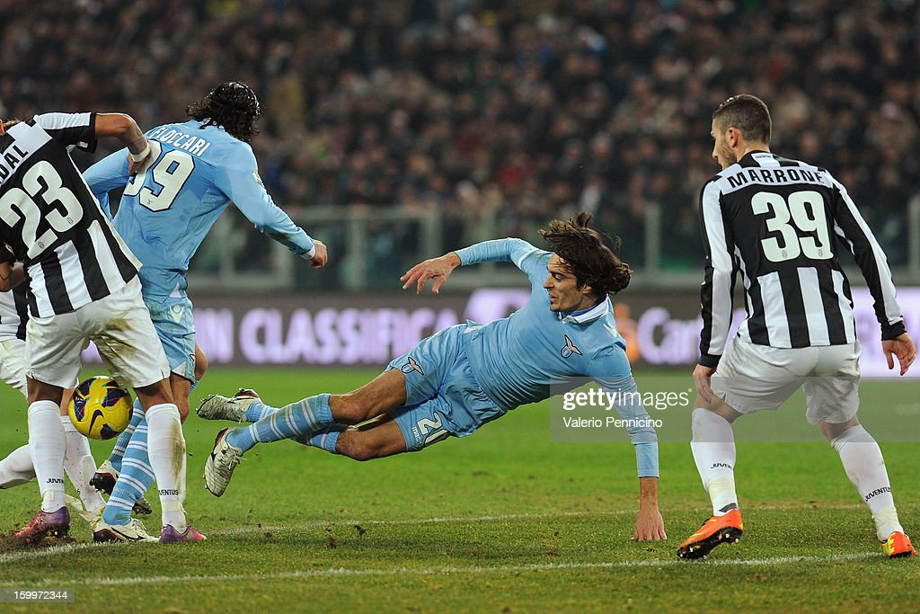Giuseppe Biava (C) of S.S. Lazio is tackled during the TIM cup match between Juventus FC and S.S. Lazio at Juventus Arena on January 22, 2013 in Turin, Italy.