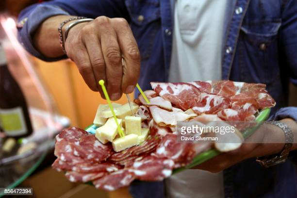Giuseppe Calà Impirotta serves a platter of local salami and cheeses at his Il Buongustaio dell'Etna wine bar on September 21 2017 in the village of...