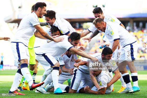 Giuseppe Panico of Italy is swarmed by teammates after scoring the game winning penalty kick during a shootout against Uruguay during the FIFA U20...