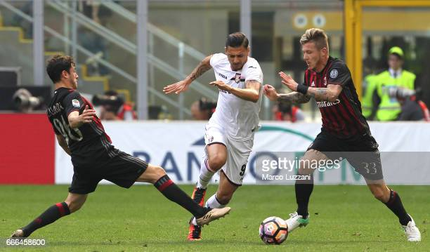 Giuseppe Pezzella of US Citta di Palermo competes for the ball with Davide Calabria and Juraj Kucka of AC Milan during the Serie A match between AC...