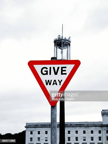 Give Way Sign With Street Light Against Cloudy Sky