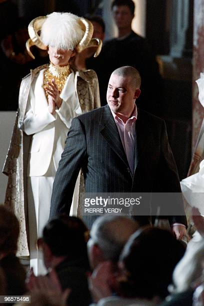 Givenchy's British designer Alexander McQueen is applauded at the end of the presentation of his spring/summer Haute Couture collections on January...