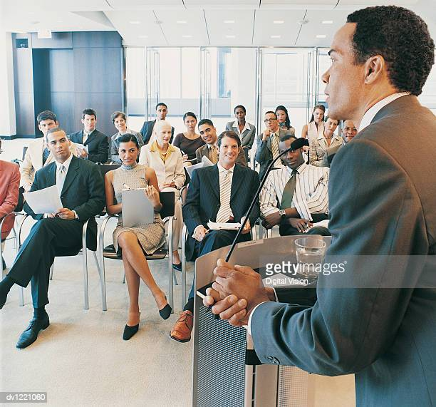 CEO Giving a Presentation to a Group of Business People from a Podium in a Conference Room