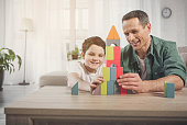 Happy man and boy are playing together at home. They are building toy tower and laughing. Friendly family concept