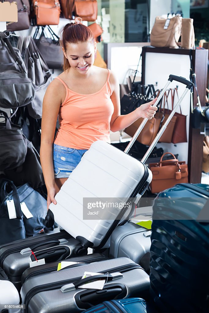 glad teenager girl choosing new large plastic luggage bag : Stock Photo