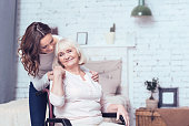 Full of grateful feelings. Smiling happy young woman standing in the bedroom and taking care of elderly disabled mother while hugging her