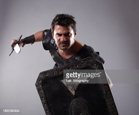 A gladiator holding an armor and a blade