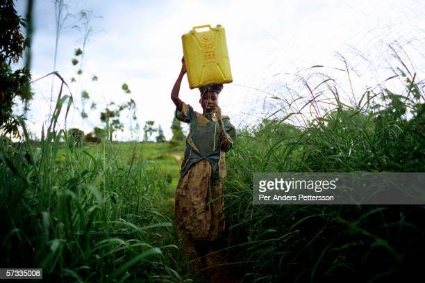 Gladys Aromo age 12 carries a container with drinking water while walking to her house on May 26 2005 in Laliya Uganda Gladys is a night commuter one...