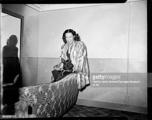 Gladys Hampton wearing fur coat standing behind sofa with 'Tempo' a Scottish Terrier dog in Stanley Theatre Pittsburgh Pennsylvania April 1944