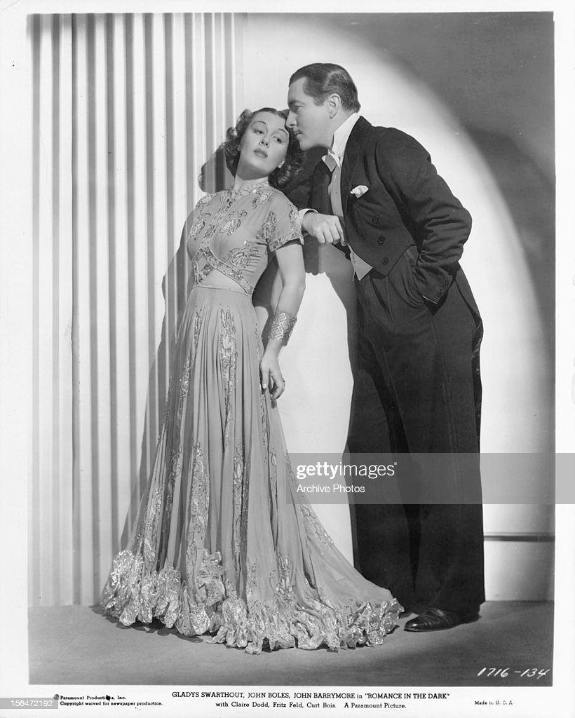 Gladys Swarthout is whispered to by John Boles in publicity portrait for the film 'Romance In The Dark' 1938