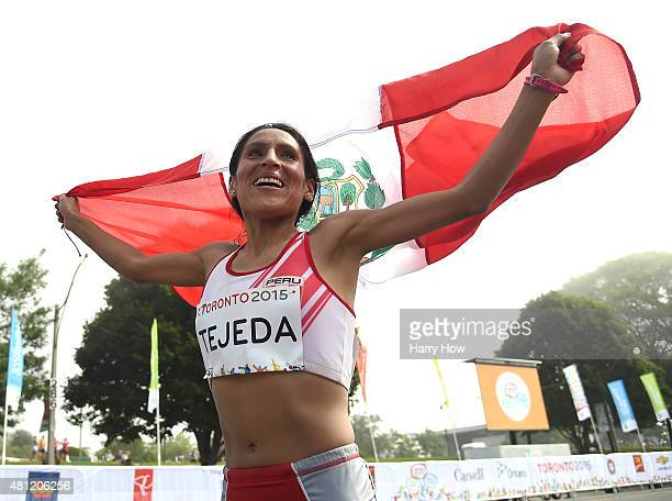 Gladys Tejeda of Peru runs with her country's flag in celebration of her gold medal in the women's marathon during the 2015 Pan Am games on July 18...