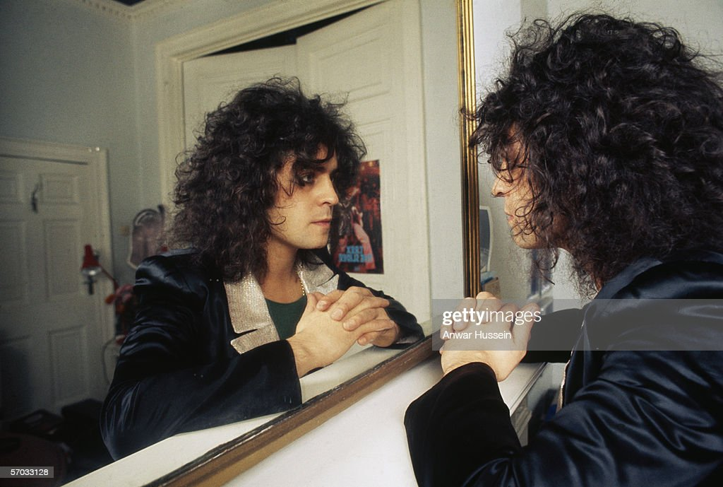 Glam rock star Marc Bolan (1947-1977) contemplates his reflection in a mirror, circa 1975.