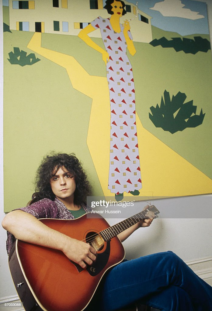 Glam rock star Marc Bolan (1947-1977) poses with a guitar in front of a painting at his home, circa 1975.
