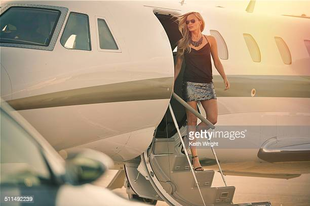 Glamorous blonde woman flying on a private jet.