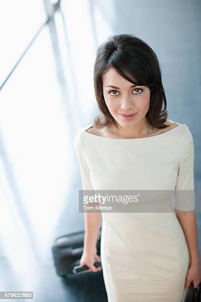 Glamouröse Geschäftsfrau ziehen Koffer